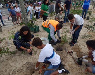 Equipe Biovert assistindo estudantes de uma escola municipal a realizarem o plantio de mudas de restinga em mutirão de plantio, na praia de Ipanema.