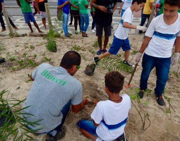 Colaborador da Biovert assistindo estudantes de uma escola municipal a realizarem o plantio de mudas de restinga em mutirão de plantio, na praia de Ipanema.